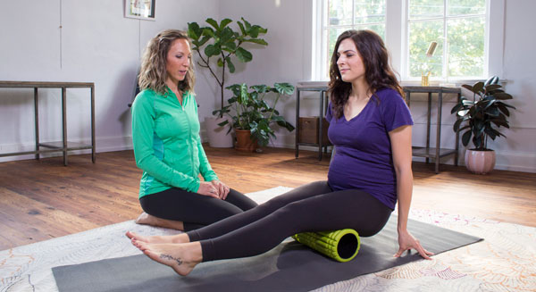 Two women exercising with a yoga mat and foam roller